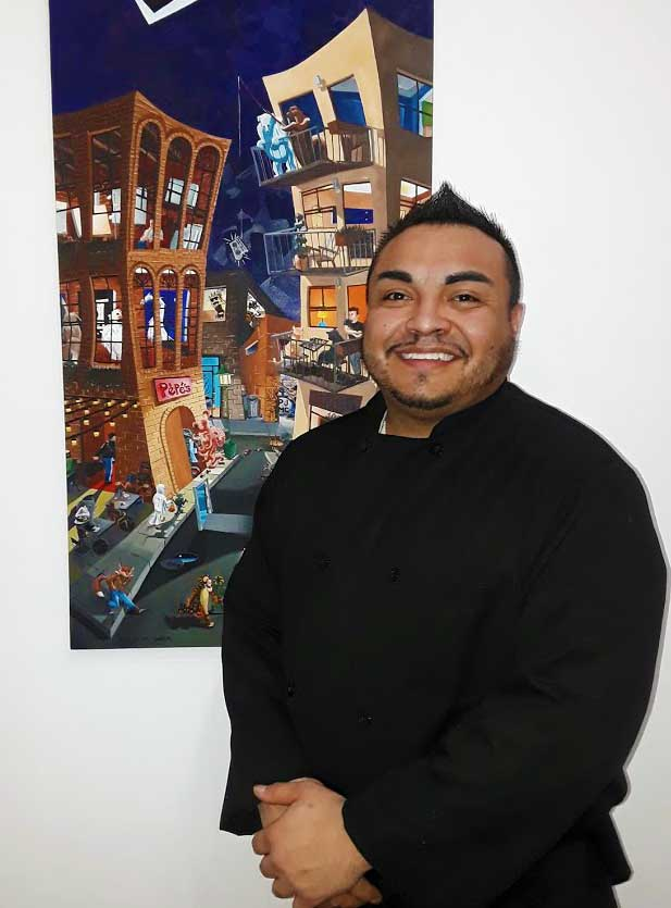 Head Chef Francisco Martinez a West Side boy, stands next to some of the art on display. Photo by JOe Contreras, Laitin Life Denver Media