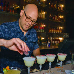 """Topher Hartfield with his Exotico cocktail """"Rosa's Cantina Sour"""" with requires a line of dried rose petals and fresh grated cinnamon."""