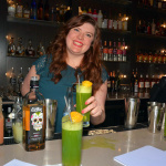 """Mattie Cowan makes green  Exotico Tequila cocktail """"Amante"""" garnished with cndied organe peel and bar cherry on rose skewer."""