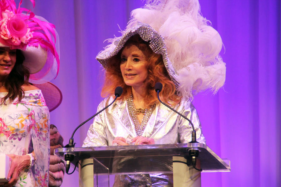 DCPA Trustee and Denver socialite Judi Wolf tells the audience they are all best in show winners for their support of the Women With Hattitude fundraiser