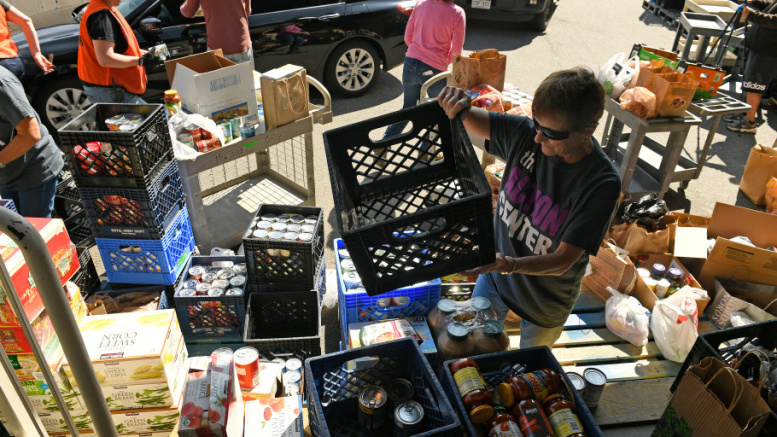 """LAKEWOOD, COLORADO - MARCH 15:  Volunteer Rosie Hughes, sorts donated food during a food drive for The Action Center on March 15, 2020 in Lakewood, Colorado. The Action Center, located at 8755 W 14thÊAvenue, is preparing to serve those in need in light of the potential emergency that COVID-19 may present in the coming weeks. From a press release the Action Center says """"should the virus begin to impact the community and create barriers to people accessing basic food needs, the Action Center will be ready for action to meet the potential increased demand."""" Dozens of cars brought lots of food that will help to fill the pantries at The Action Center.  The Action Center serves 80 families a day and 20,000 families each year. (Photo by Helen H. Richardson/The Denver Post)"""