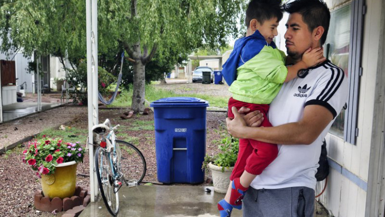 latino-man-with-child-amid-coronavirus-covid-19-fears-via-AP-Photo